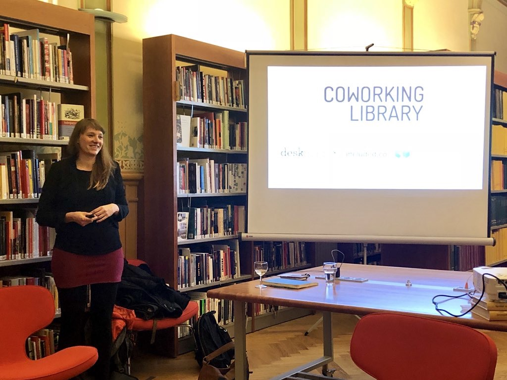 Johanna presents an update on the Coworking Library in an actual library in Amsterdam, next to her is a presentation with the title Coworking Library